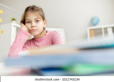 Bored little schoolgirl leaning by her hand while sitting by workplace in school