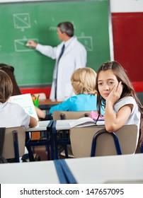 Bored little schoolgirl sitting at desk with teacher teaching geometry in classroom
