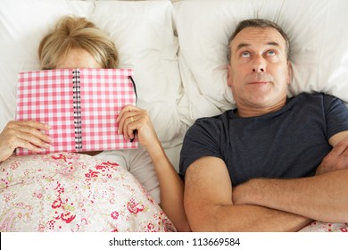 Bored Looking Senior Man Lying In Bed Next To Senior Woman Reading Book