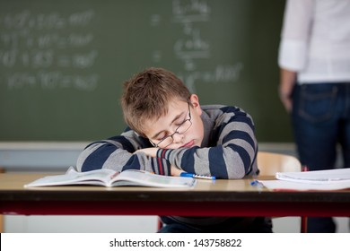 Bored male student sleeping at desk while teacher standing in background