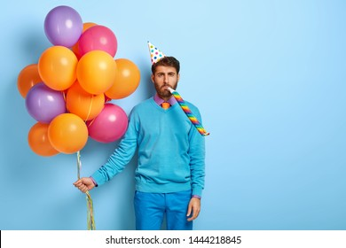 Bored man blows party horn, feels tired after noisy birthday party, wears paper cone hat, congratulates brother with anniversary, stands with colorful balloons, isolated on blue wall. Holiday concept