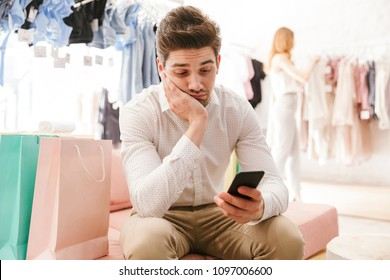 Bored man holding mobile phone while his girlfriend shopping for clothes on a background