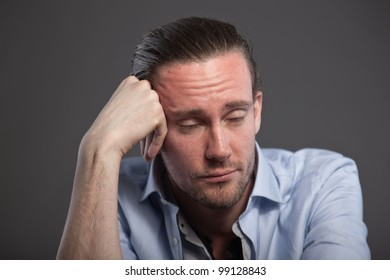 Bored man with long hair and expressive face wearing blue shirt. Isolated on grey background.