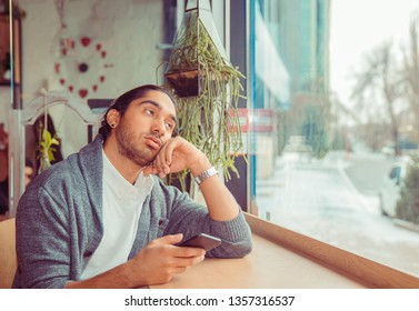 Bored man looking up tired holding phone in hand in boredom. Closeup portrait of handsome guy wearing white shirt, gray blouse sitting near window at a table in living room or coffee shop. Mixed race