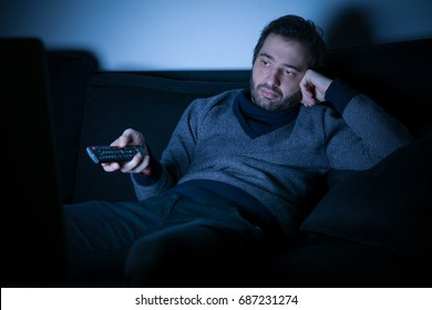 Bored man watching television at night lying on the couch