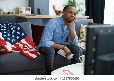 Bored man watching TV with information about election