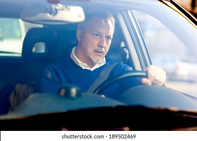 Bored mature man driving his car