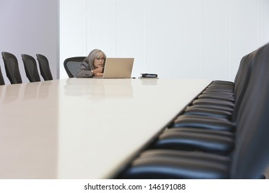 Bored middle aged businesswoman looking at laptop screen in board room