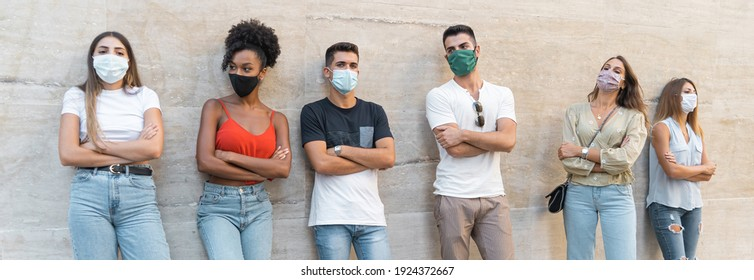 Bored multiracial young people with coronavirus face mask standing against a concrete wall and arms crossed
