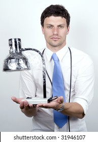 A Bored office worker holds a lamp he has wrapped in cello-tape