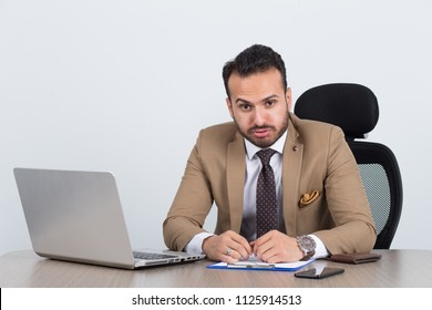 Bored overworked businessman at work blowing his mouth annoyed.