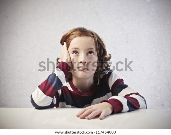 A bored red child is thinking while is leaning on a white desk