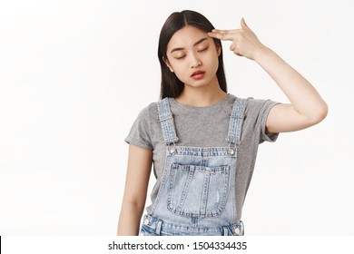 Bored reluctant asian dark-haired girl cannot stand boring talk close eyes hold finger pistol shoot herself commit suicide boredom uninteresting event sighing exhausted reluctant white background