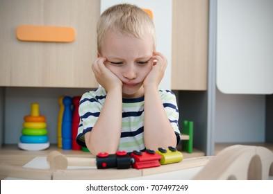 Bored sad little boy sitting at table. sad bored boy child toy activity baby kindergarten concept