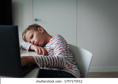 Bored and sad teenager looking at computer, kid tired of online communication and learning