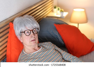 Bored senior woman lying in bed