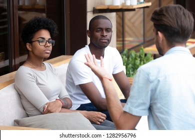 Bored serious black married couple sitting together on couch visiting medical specialist listening psychologists counselor feeling disinterested and mistrust to methods of psychological assistance