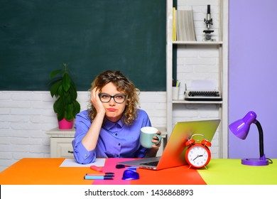 Bored student girl preparing for exam. Educational process. Tired teacher works with laptop in classroom. Student learning in auditorium. Female student thinking about coursework. Back to school.
