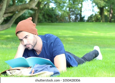 Bored student reading his notebook on campus