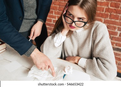 Bored student rolling her eyes at study. Beautiful young woman ignoring her teacher. talking next to her. Education, boredom, private lessons, extra-curriculum, routine concept