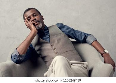 bored stylish african american man in waistcoat sitting in armchair