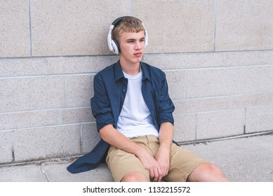 Bored teen sitting on the ground against a wall while listening to music through headphones.
