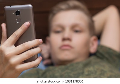 Bored teenager boy holding a cell phone in hand. Bored teenager looking at smartphone.