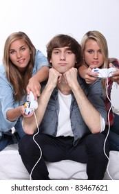 Bored teenager sat between two friends playing video games