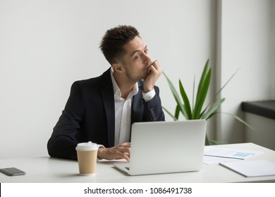 Bored tired millennial businessman in suit feeling dull working on laptop at workplace, absent-minded employee thinking or boring monotonous office routine, no motivation and lack of ideas concept
