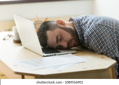 Bored tired office worker falling asleep on laptop, person tired after long working hours, exhausted because of increased workload. Concept of overwork, stress, boredom, no motivation, lack of sleep