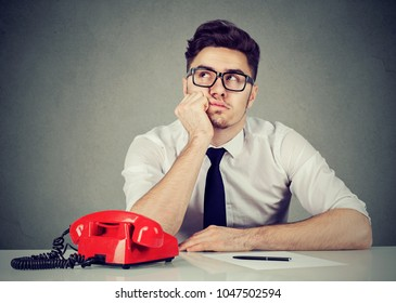 Bored uninspired corporate employee sitting in his office daydreaming