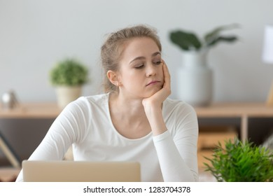 Bored unmotivated millennial woman thinking of dull work disinterested in study on laptop, lazy absent-minded girl student wasting time tired of monotonous routine, boredom and lack of ideas concept