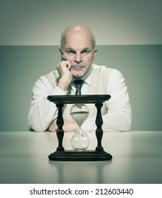 Bored vintage businessman waiting at desk with hourglass.