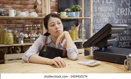 bored waitress girl in apron sitting in cafe bar counter with hand in chin looking out store. depressed coffee shop owner with no customer visiting. unhappy lady worried about small startup business