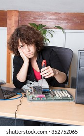 Bored woman fixing a computer at work