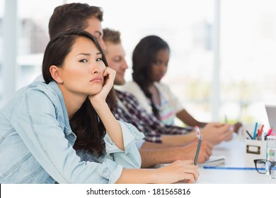 Bored woman looking at camera during a meeting in creative office