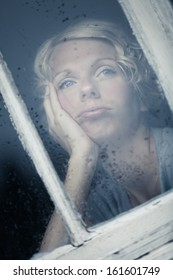 Bored Woman Looking at the Rainy Weather By the Window Frame