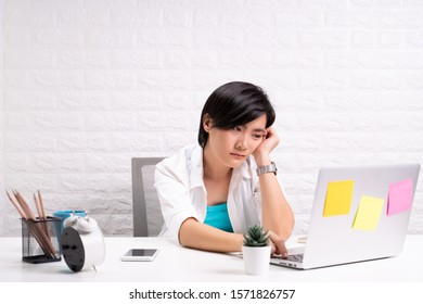 Bored woman at office working with a laptop