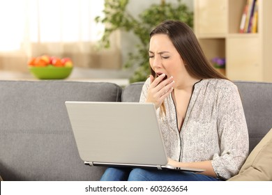 Bored woman on line yawning sitting on a sofa in the living room at home