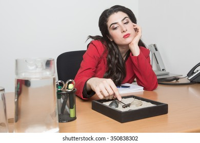 Bored woman sitting in the office playing with zen garden sand while thinking, she has her hand in her head and is wearing a red jacket