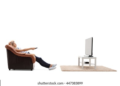 Bored woman sitting on an armchair and watching TV isolated on white background