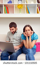 bored woman sitting while her boyfriend playing video game