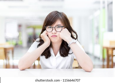bored young asian female student, bad mood after learn after class in education, with desk in library of university in a concept of learn, education and lifestyle