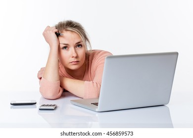 bored young blond woman leaning her head and lying on her white sparse desk, working hard on her laptop, isolated white background