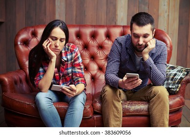 bored young couple sitting on couch and looking at their phones