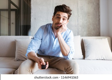 Bored young man holding tv remote control while sitting on a couch at home