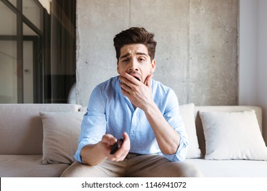 Bored young man holding tv remote control while sitting on a couch at home, yawning