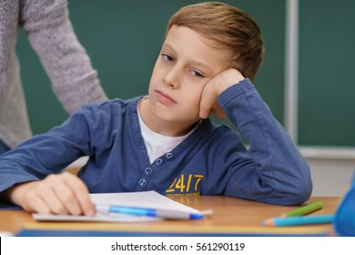 Bored young schoolboy sitting in class with his head resting on his hand looking to the side oblivious to his teacher approaching from behind