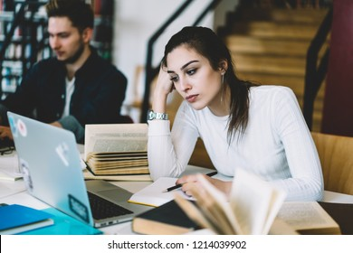 Bored young woman watching tutorial online on laptop computer preparing coursework project in college library,unhappy female student tired with learning disappointed with bad wifi connecting in campus