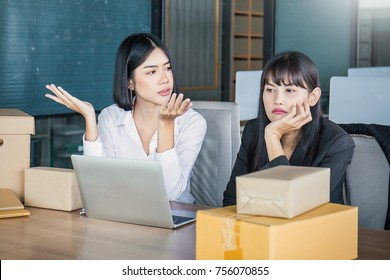 Bored,two business woman sitting discussion on the desk. Freelance woman working overload, Young Asian small business owner at home office, online marketing packing box and delivery, SME concept